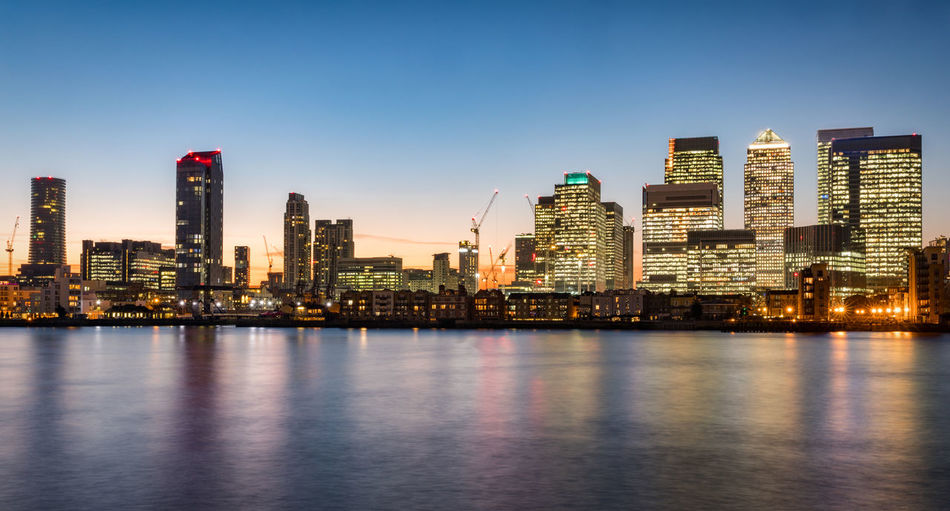 Modern buildings by thames river at canary wharf during sunset in city