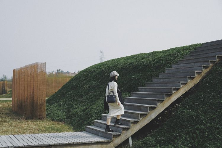 Rear view of man standing on staircase against sky