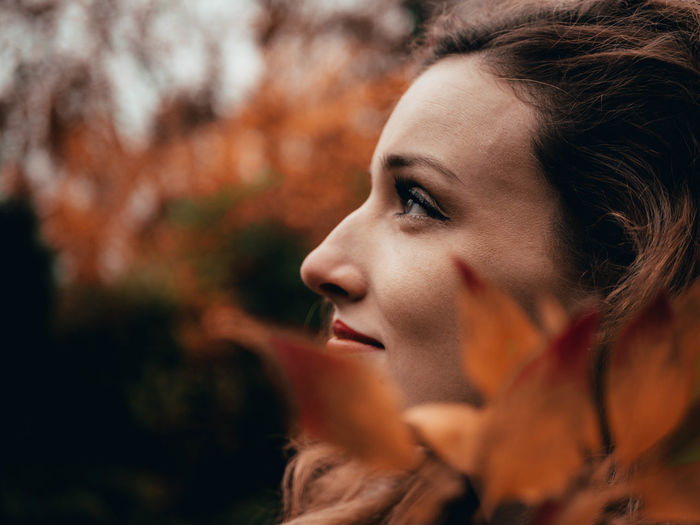 Side view of thoughtful young woman looking away at park during autumn