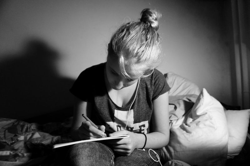 Young Woman Writing In Book While Sitting On Bed At Darkroom