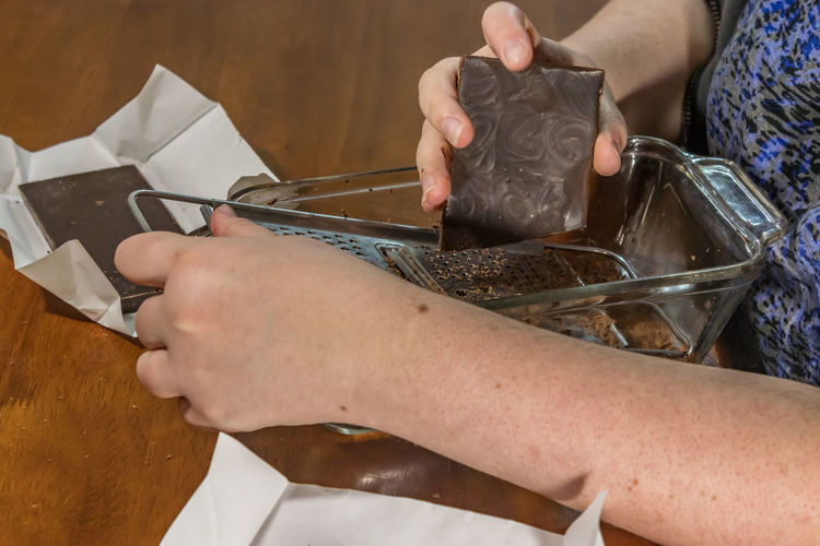 Midsection of woman grating chocolate in container while sitting at home