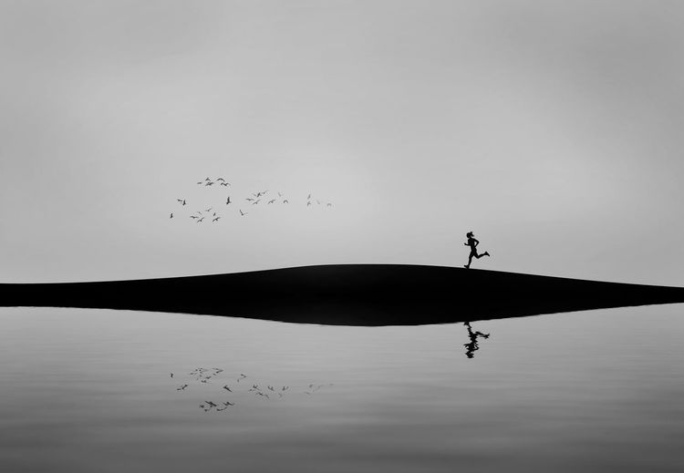 Silhouette woman running on sand dune by reflection in lake against sky