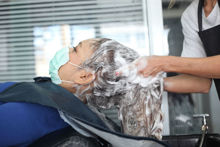 Midsection of hairdresser washing woman hair in salon