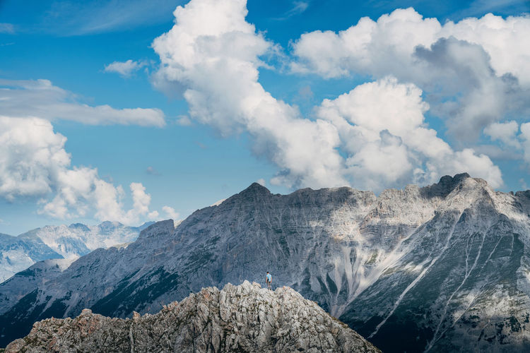 Distant view of hiker on mountain peak against cloudy sky