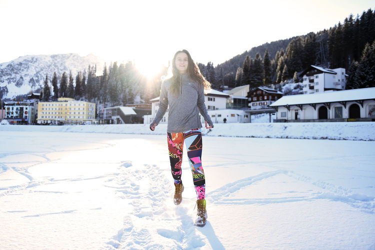 Full length of woman walking on snow covered land