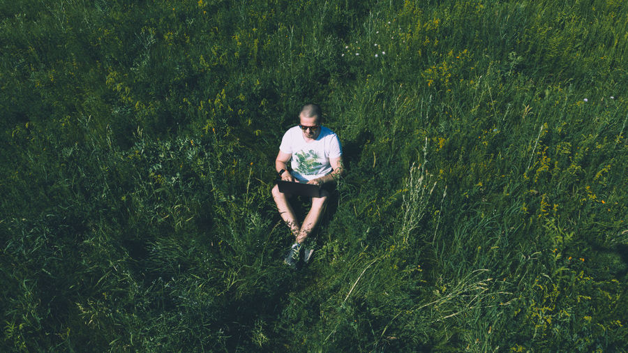 High angle view of man using laptop while sitting amidst grass
