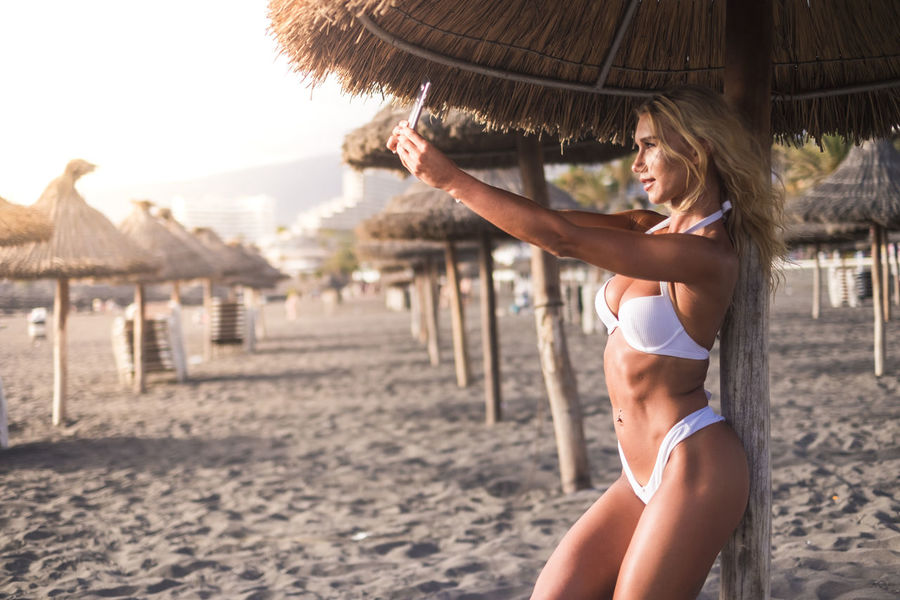 perfect body blonde model taking selfie picture in vacation at the beach under the umbrella sun. sunset time during a summer holiday. enjoy the nice weather at the resort Abdominal Muscle Adult Backgrounds Beach Beautiful Woman Beauty Bikini Building Exterior Day Female Focus On Foreground Hair Hairstyle Leisure Activity Lifestyles Nature One Person Outdoors Real People Sand Sexywomen Straw Umbrellas Tenerife Island Young Adult Young Women