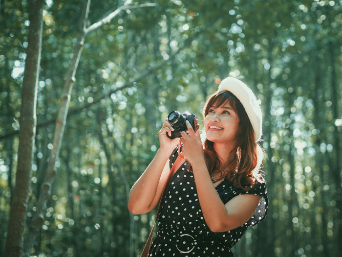 Beauty Camera - Photographic Equipment Cheerful Day Enjoyment Forest Fun Happiness Holding Leisure Activity Lifestyles Nature One Person One Woman Only Outdoors Photographer Photographing Photography Themes Smiling Standing Summer Tree Women Young Adult Young Women