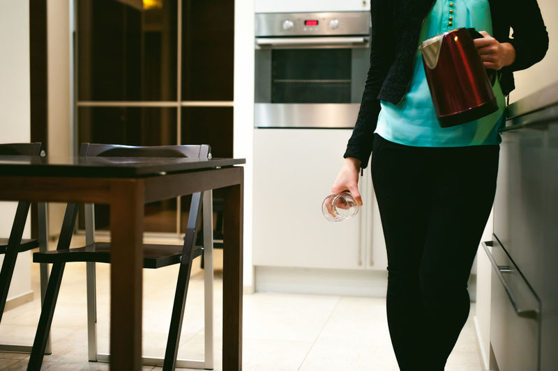 Midsection Of Woman Holding Glass And Jug While Standing At Home