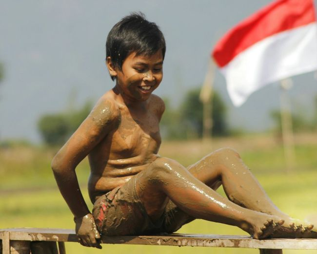 Full length of shirtless boy sitting with indonesian flag in background