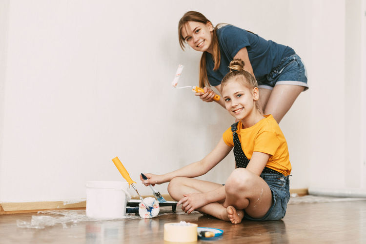 A girl with her sister in bright blue and yellow clothes helps to paint the walls in her room white.