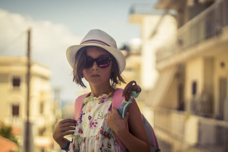 Girl wearing sunglasses standing against sky in city