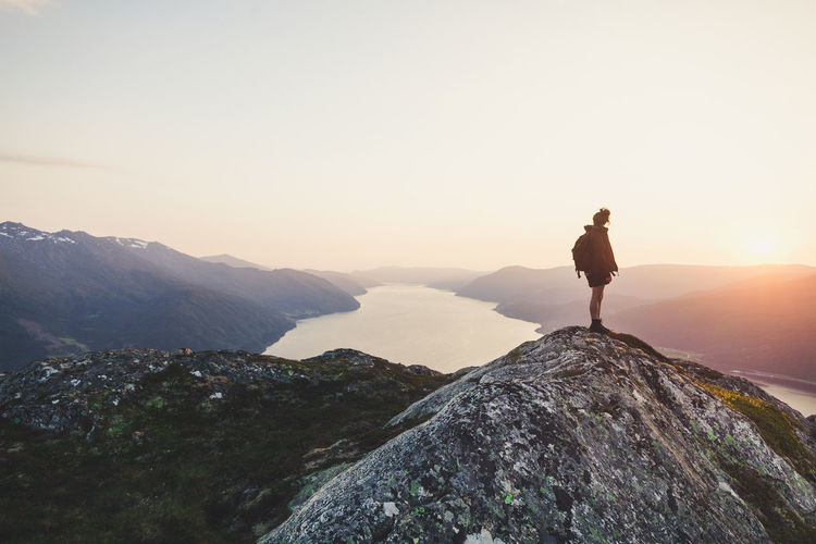 Rear View Of Woman Looking At River Amidst Mountains Against Sky During Sunset