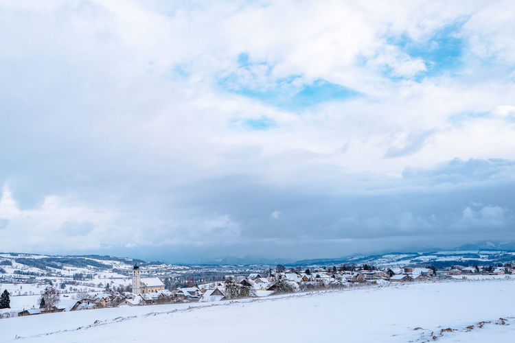 View Of Snow Covered Residential District Against Cloudy Sky At Knutwil