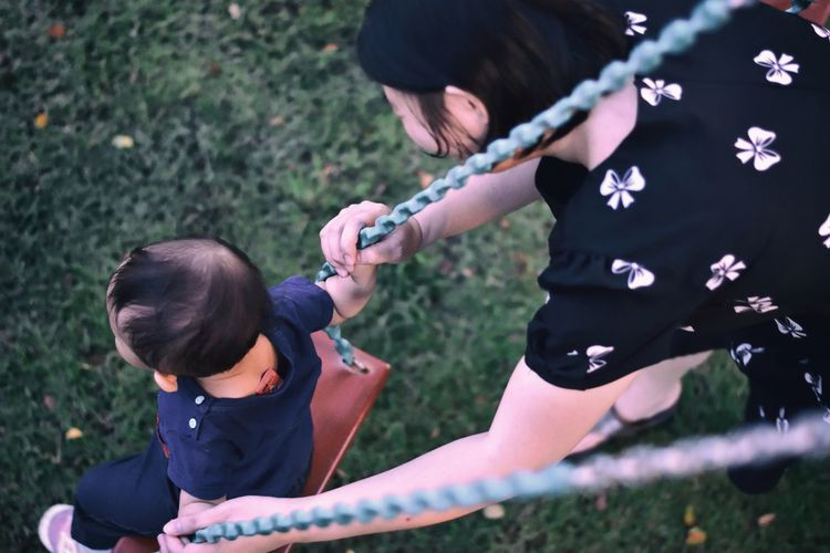 High angle view of mother swinging child at playground