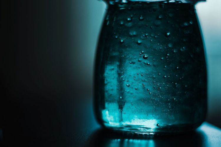 Close-up of wet glass against blue background
