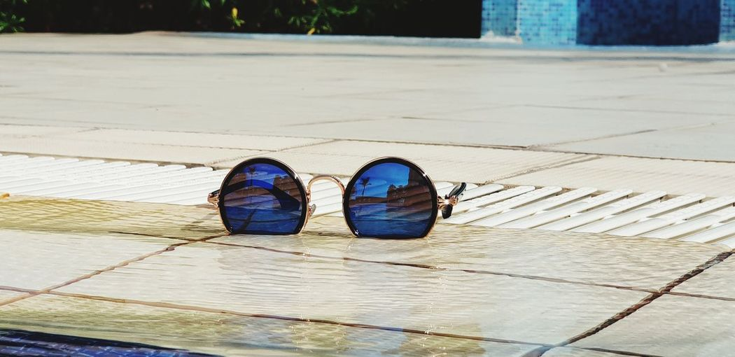 Close-up of sunglasses at poolside