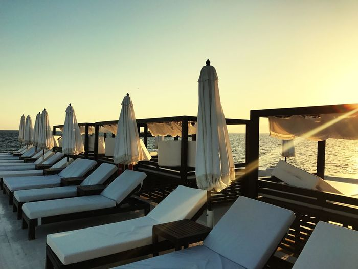 Umbrellas Day Bed White Color Stylish Furniture Sky Clear Sky Architecture Nature Water Built Structure Sunset No People Sea Sunlight Outdoors
