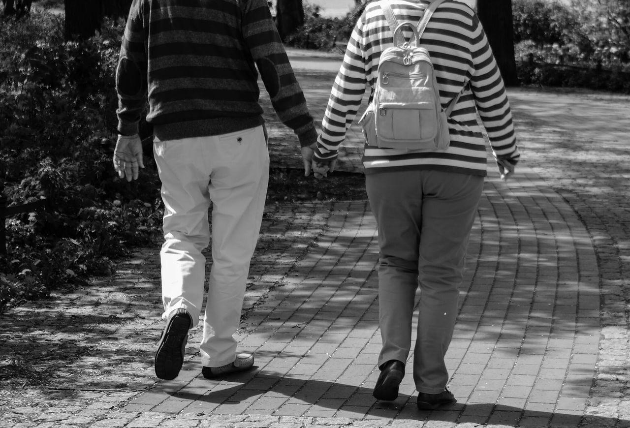 Low Section Of Couple Walking On Footpath In Park