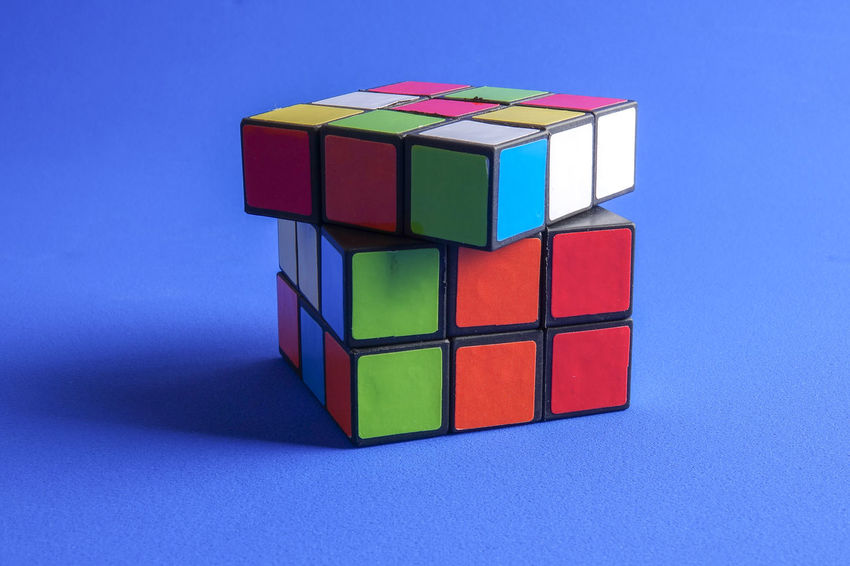 RUBIK'S CUBE , CREATIVITY TOY Creativity Rubik Cube Balance Block Blue Blue Background Close-up Colored Background Cube Shape Cut Out Design Geometric Shape Indoors  Intelligence Multi Colored No People Red Rubik Shape Stack Still Life Studio Shot Toy Toy Block