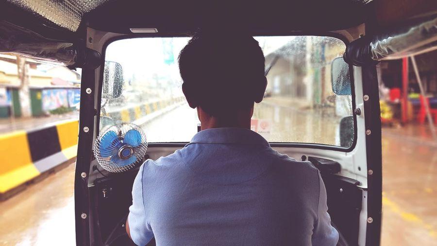 Rear view of man driving jinrikisha on street