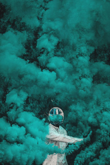 Man wearing helmet holding distress flare while standing amidst smoke