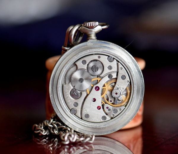 Close-up of clockworks on table