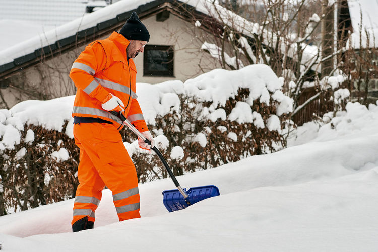 Low angle view of man working on snow
