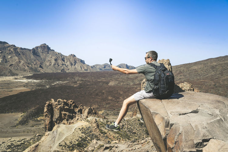 Man taking selfie with camera while sitting on cliff against mountains