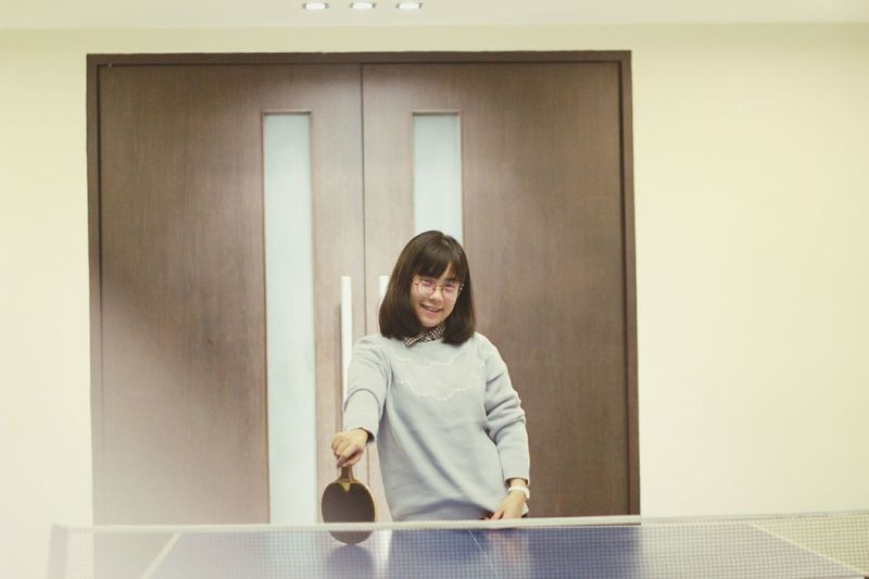 Portrait of young woman holding table tennis racket at home
