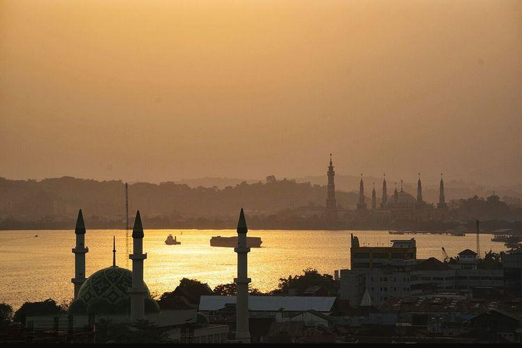 Masjid baitul muttaqin by mahakam river against clear sky during sunset