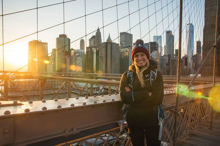 Young female on Brooklyn Bridge with sun setting behind downtown Manhattan sky scrapers NYC New York City Architecture Building Exterior Built Structure City Connection Day Front View Lifestyles Looking At Camera One Person Outdoors People Portrait Railing Real People Sky Skyscraper Standing Suspension Bridge Warm Clothing Women Young Adult Young Women