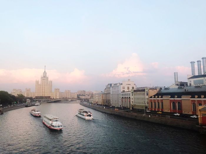 View of buildings at waterfront against cloudy sky