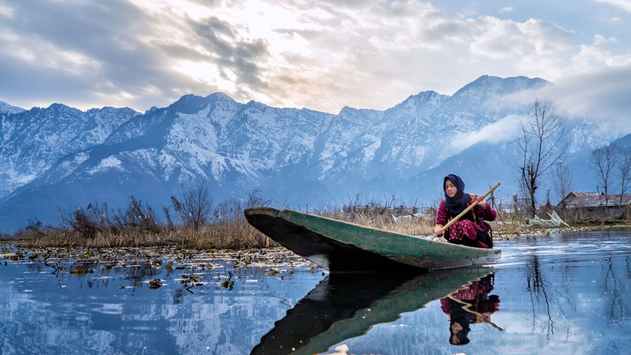 Woman rowing boat in lake against snowcapped mountains
