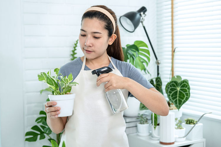 Young woman holding white while standing by potted plant