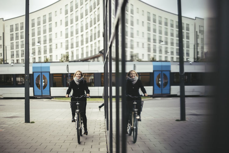 Man and woman on bicycle in city