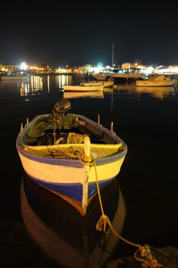 Boats moored in harbor at night