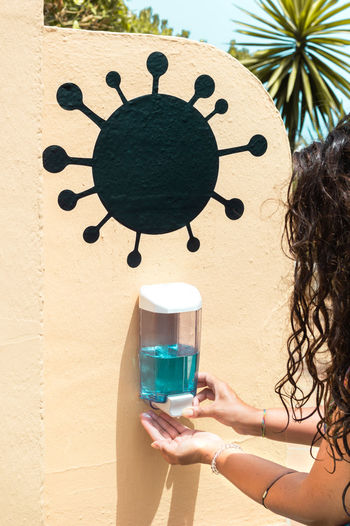 Cropped hand of woman using hand sanitizer outdoors
