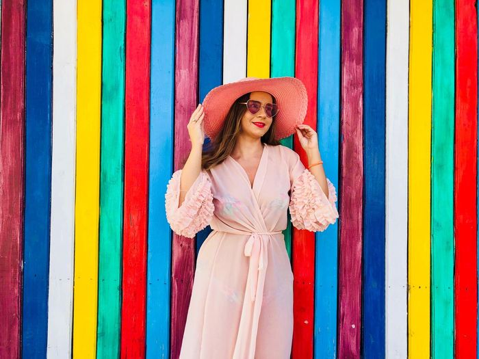 Woman wearing pink dress, pink hat and fashionable sunglasses standing in front of a colorful vertical striped wall Beach Hairstyle Bright Colors Vibrant Color Bright Vertical Colors Colorful Striped Stripes Wood - Material Wooden Wall Pink Fashion Allpink Pink Sunglasses Sun Hat Hat Dress Accessories Clothing Beachwear Style Fashion Young Adult Standing Woman Summer