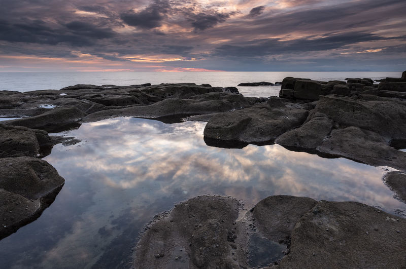 Moody coastal reflections at dusk Weather Beauty In Nature Cloud - Sky Horizon Over Water Idyllic Land Moody Nature No People Non-urban Scene Reflection Rock Rock - Object Rock Formation Rock Pool Scenics - Nature Sea Sky Solid Sunset Tranquil Scene Tranquility Water Waves Wild