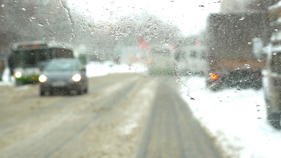Cars on road seen through wet glass window
