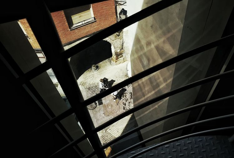 Low angle view of silhouette people on glass building