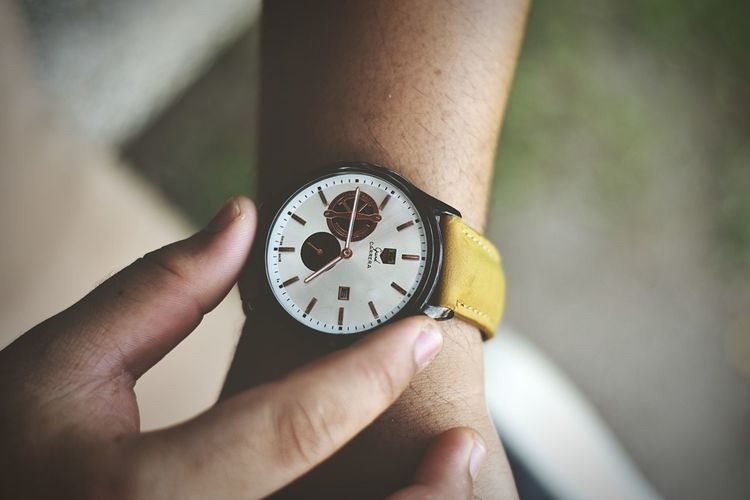 Close-up of hand holding clock against blurred background