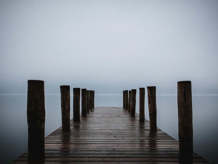 Wooden pier on sea against sky