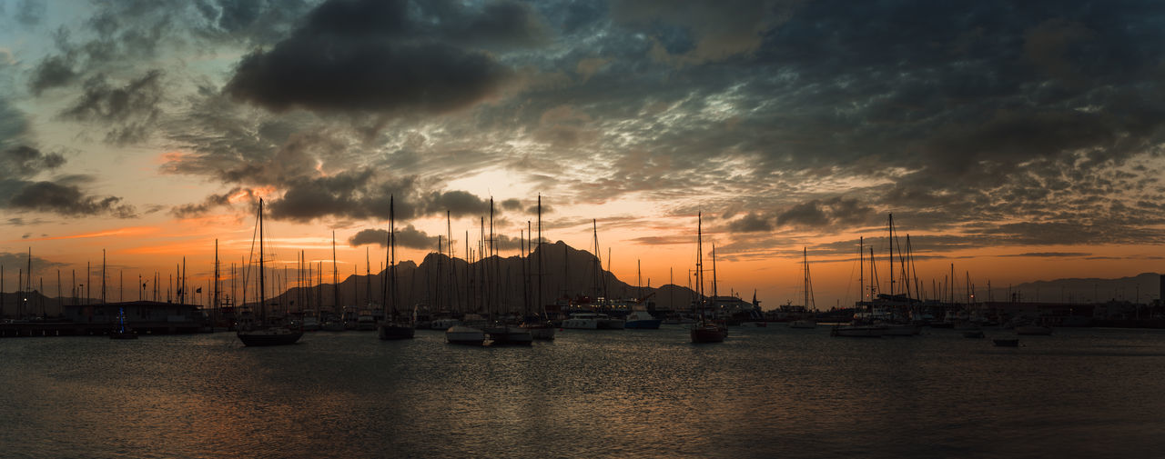 Colorful dawn over Monte Cara mountain in hardor of Mindelo. Sao Vicente Cape Verde. Cape Verde Cloudscape Golden Harbor Shape Silhouette Sunlight Tranquility Twilight Yachts Beauty In Nature Dusk Firered Golden Hour Horizon Lagoon Landscape Mindelo Mountain Sailboat Seascape Shelter Sunset Tourism Vibe