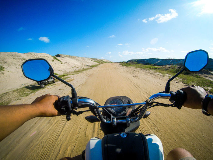 Cropped image of man riding motorcycle on dirt road