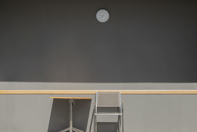 Low angle view of clock on table against wall