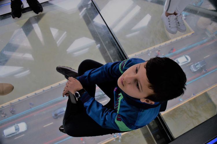 Boy Looking Away While Sitting On Glass Floor