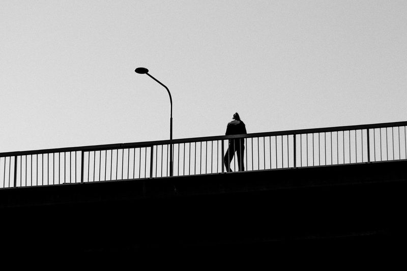 Rear view of silhouette man standing on bridge against clear sky