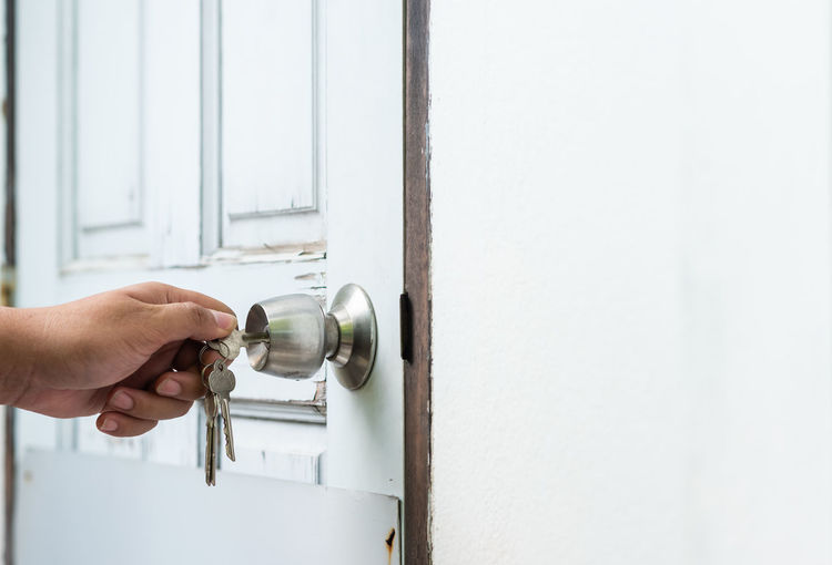 Cropped image of hand unlocking door with key
